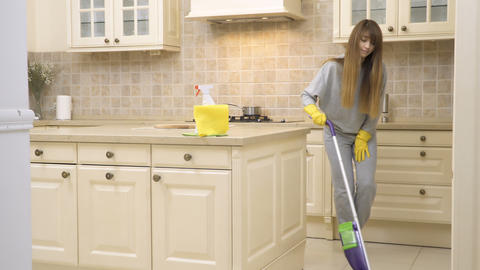 Young housewife cleans kitchen floor with mop Footage