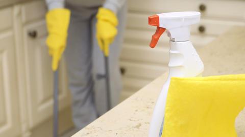 Woman sweeps kitchen floor Footage