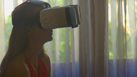 Girl Puts on Virtual Reality Helmet by Window in Room Closeup 영상물