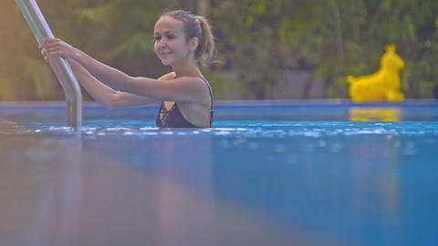 Slim Blond Girl Plunges into Pool against Green Plants Closeup Footage
