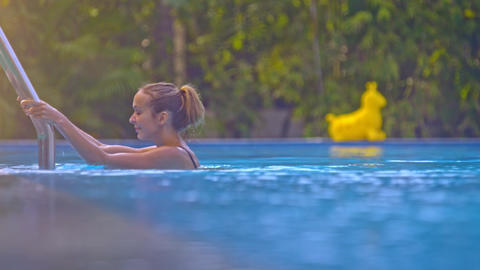 Slim Girl Gets out of Pool against Green Landscape Closeup Footage