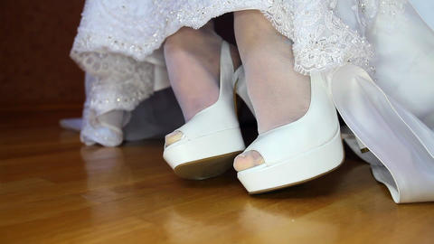 Bride Lows Wedding Dress Hem and Hides White Shoes Closeup Footage