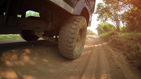 Low Angle Perspective of Wheel Rolling over Dirt Road. with Sound Footage