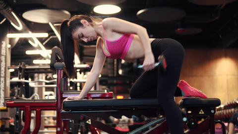 sports girl doing exercises with dumbbells in the gym. sexy girl in sportswear Footage