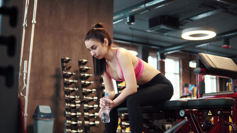 slender sexy girl is drinking water from a bottle in the gym. Sportswoman in ビデオ