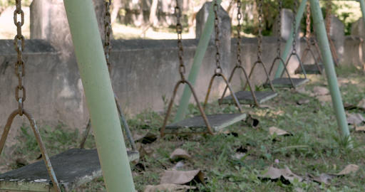 A single swing moving back and forth on a rusty swing set in an abandoned Footage