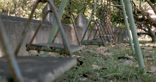 Handheld low angle of a swing moving back and forth in abandoned playground Footage