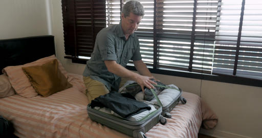 Tourist man having trouble fitting all his belongings in his suitcase so he Footage