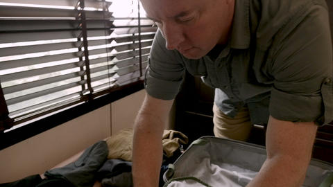 Handsome middle aged man packing his clothes in his travel bag preparing for a Footage