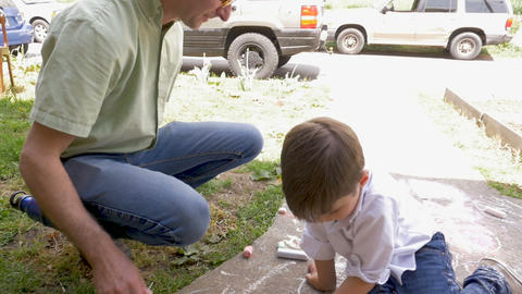 Father and son playing together with chalk outside in slow motion on a sidewalk Footage