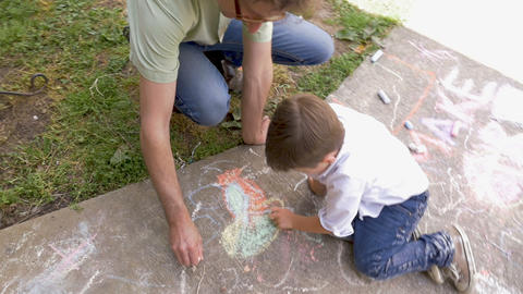 Overhead shot of a man and young boy coloring and drawing with chalk on a Footage