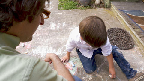 Adorable young boy with chalk all over his pants drawing with his father outside Footage