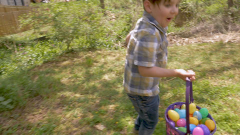 Happy excited young 4 - 5 year old cute boy holding a basket filled with easter Footage