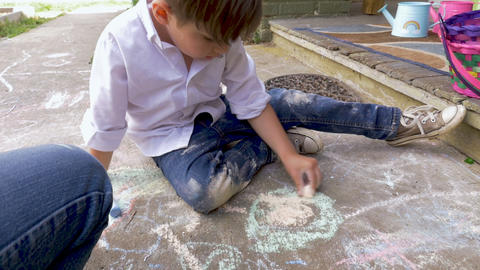 4-5 year old boy drawing with chalk with his dad using his left hand outside in Footage