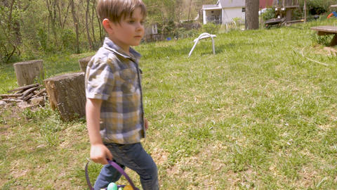 Excited 4 - 5 year old boy running to get an easter egg before another boy in Footage
