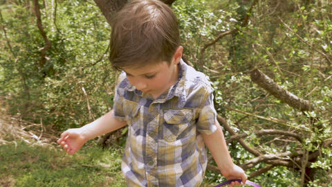 Cute young boy 4 - 5 years old holding an Easter basket walks towards his mother Live Action
