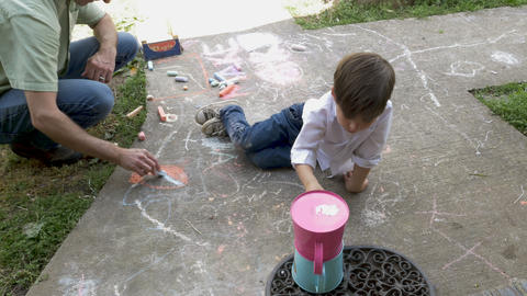Overhead of a young 4 - 5 year old boy helping an adult man color with chalk on Footage