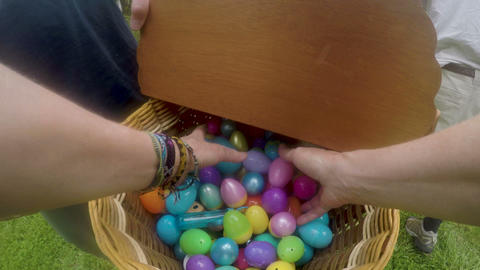 POV of a woman's hands reaching into an Easter basket and grabbing plastic Live Action