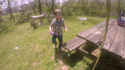 Happy healthy young 4 - 5 year old boy running and collecting Easter eggs Footage