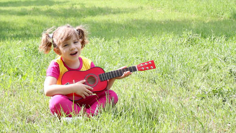 Little Girl Sitting On Grass And Play Guitar stock footage