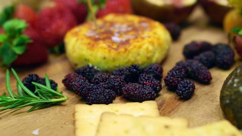 Cheese with strawberry, berries and fruits on wood platter Footage