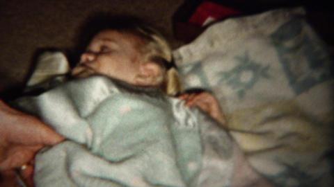 1961: Mom tucking in baby girl blanket sucking thumb bedtime Footage