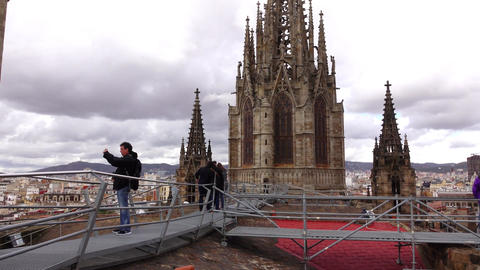Tourists at roof of Santa Cruz Cathedral, tilt down from spiked tower to roof Live Action