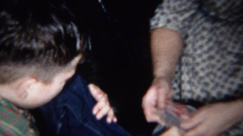 1959: Boy takes off socks and shoes and mom puts back on Footage
