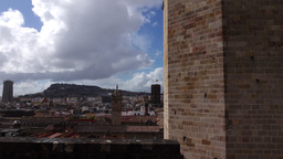 High contrast cityscape panorama reveal from behind tower wall, slide shot Live Action