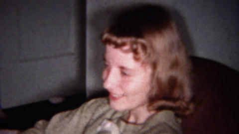 1959: Short hair bangs teenage girl shyly smiles sitting on couch Footage