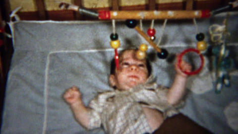 1958: Baby plays wooden mobile rings above crib bed Footage