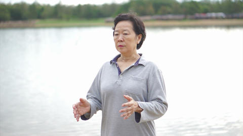 Video of Asian Senior Elderly Practice Taichi, Qi Gong exercise outdoor next to  Footage