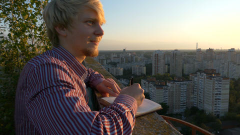 4k - Young writer finding his muse on the roof of skyscraper at sunset Live Action