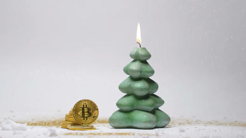 Pine Shape Candle and Bitcoins with Artificial Snow Closeup Footage