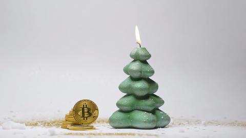 Christmas Burning Candle and Gold Bitcoin on Rib Closeup Image