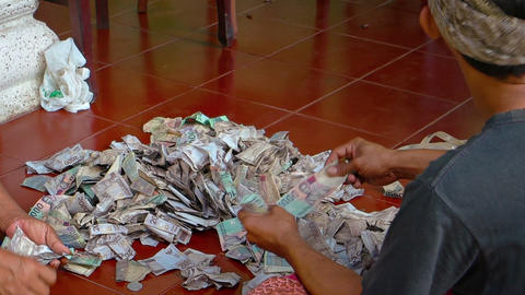 Locals counts small money - begging at temple Pura Goa Lawah. Bali. Indonesia Footage