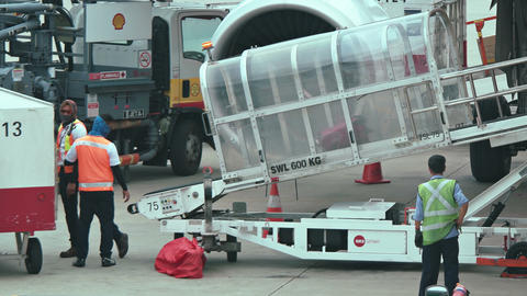 Ground Crew Unloading Bags at Changi International Airport in Singapore Footage