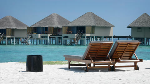 Sun loungers on tropical beach resort in Maldives. with bungalows in background Footage