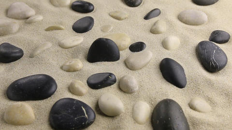 Zoom of a black stone standing in the sand among the garden of stones Live Action