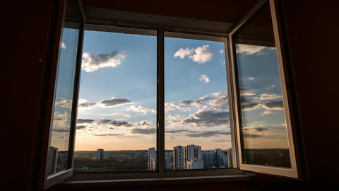 Sunset clouds through a window with a reflection in the window casement Footage