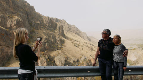 Daughter taking photo by mobile phone of her senior parents on vacation trip in Footage