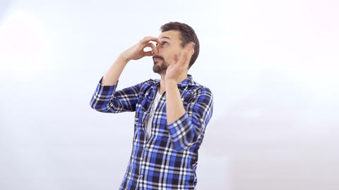Man pinches his nose from a stink at white background Footage