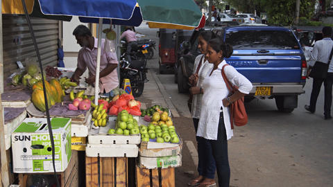 Local vendor sells fruit and produce on typical sidewalk in Colombo. with sound Footage