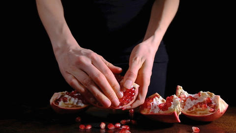 Female hands peeling a pomegranate on a dark background, pomegranate seeds Footage