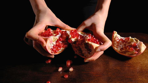 Female hands break the half a ripe pomegranate in half on a brown Desk and dark Live Action