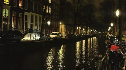 Typical Amsterdam canal and houses alongside embankment at night, the Footage