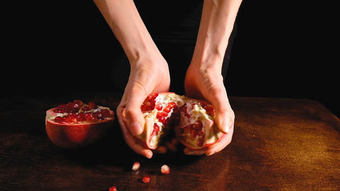 Female hands break the half pomegranate in half on a brown Desk and dark Live Action