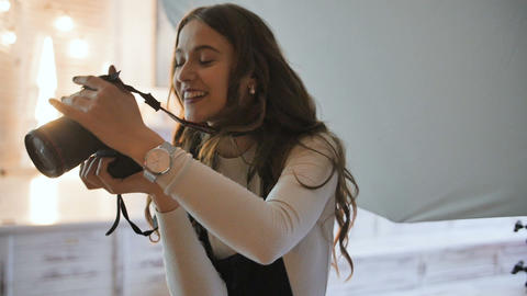 Young beautiful photographer with the professional camera. Shooting, laughing Footage