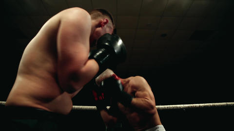 In the boxing ring, two men in boxing gloves are fighting. Dynamic camera Footage