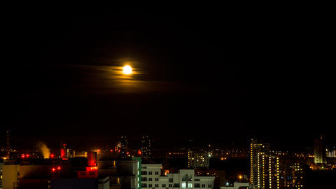 The moon rises above the lights of the night city. Time Lapse Footage